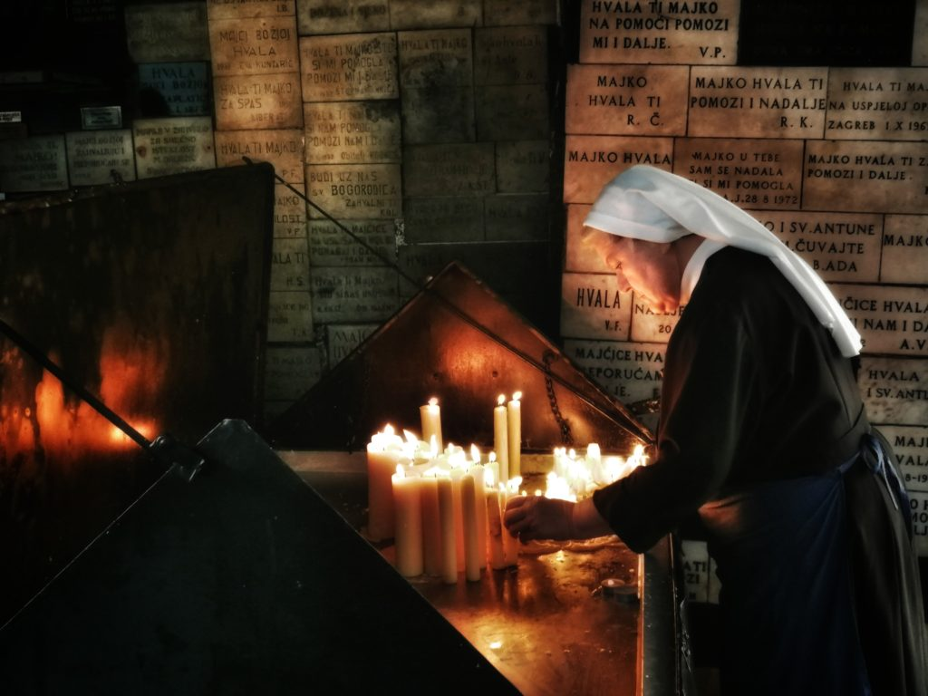 A nun lights up the candle at Stone Gate