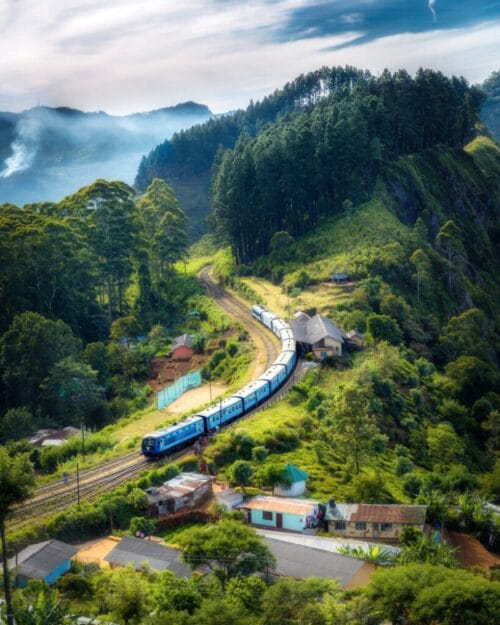 long train going through green mountains with small houses and villages