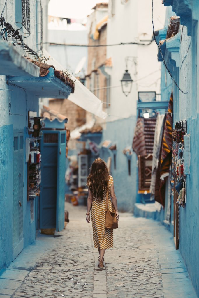 woman walking through cobblestone street with colorful shops around her