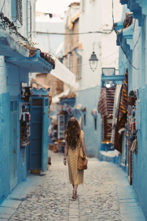 woman walking through cobblestone street