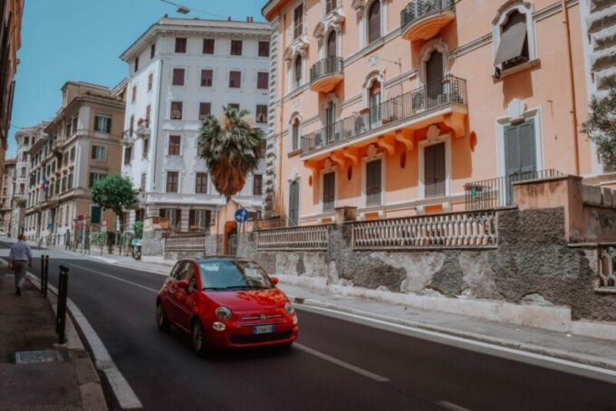 apartment in sunny Italy on narrow street with red fiat driving by