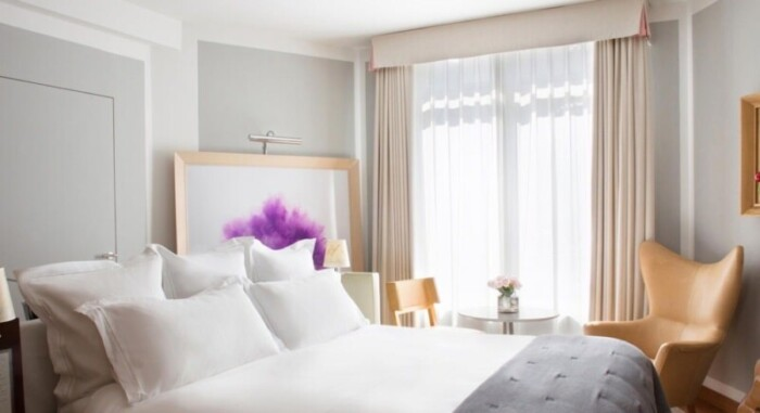 Le Royal Monceau Raffles Paris' deluxe Collection Room in grey and white with art.