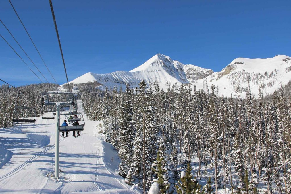 mountain in sky with ski slope and ski lift in forefront.
