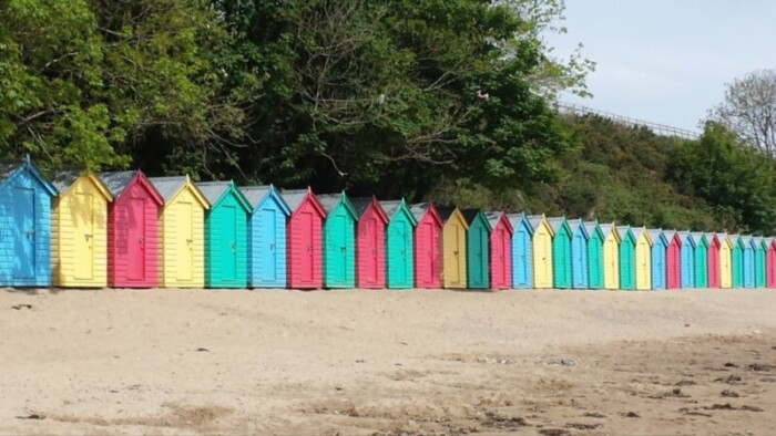 Colorful beach huts line the shore.