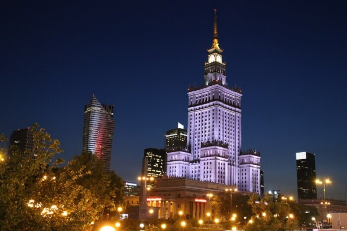 The Palace of Culture and Science in Warsaw, Poland at night, lit up in purple.