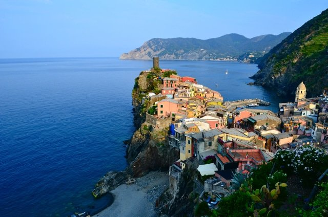 Aerial view of Corniglia, Cinque Terre - colorful houses inside of a cliffside on the ocean.