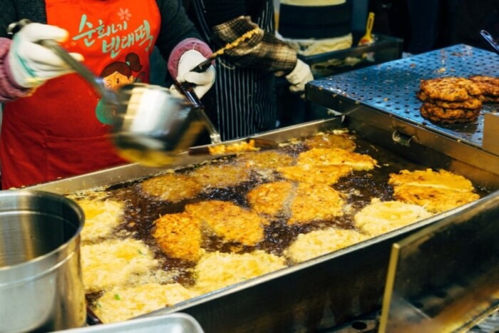 A lady cooking korean seafood pancakes