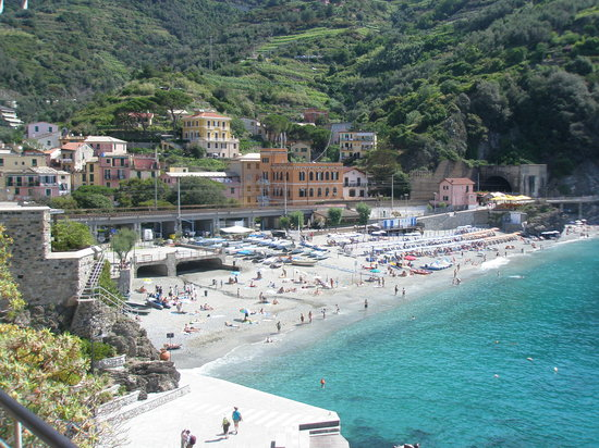 public beach in Monterosso - Cinque Terre - light blue water on pale beach with visible people and sunbeds and large orange building in back.
