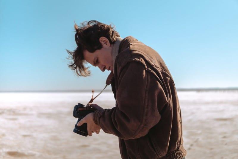 Man wearing brown jacket holding a camera