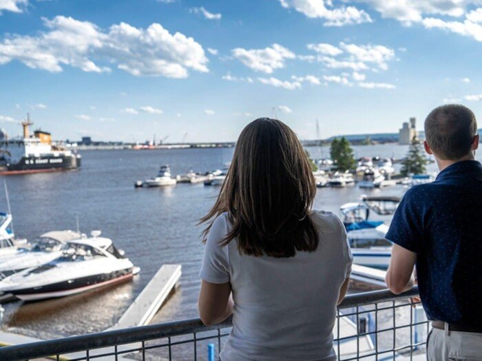 A couple admires the view from their Park Point Marina balcony.
