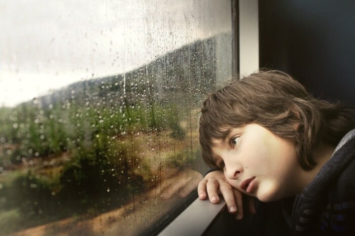 Sad kid looking out of the car window