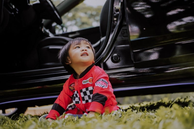 Toddler sitting on the grass with a vehicle behind him