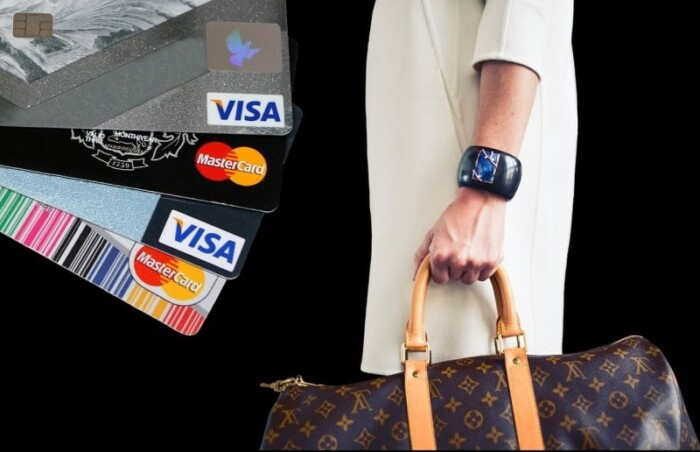 Woman holding a travel bag with credit cards