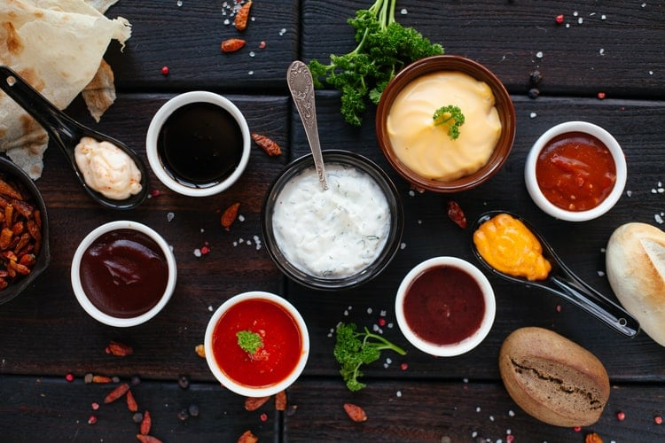 A ranch dressing surrounded by six other sauces