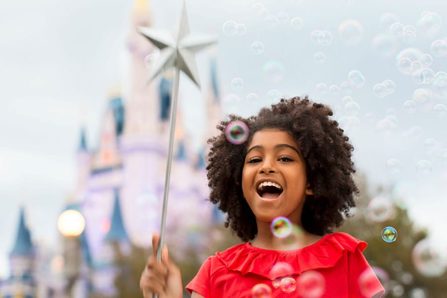 Young girl blowing bubbles in amusement park
