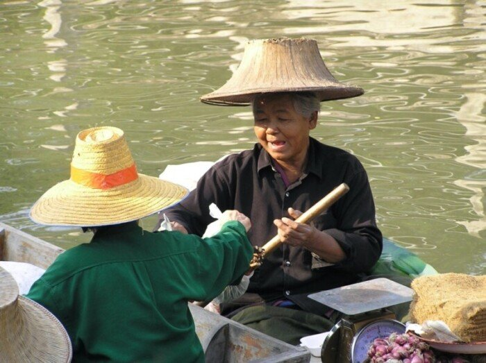 A woman sells food in a typical floating market in Thailand.
