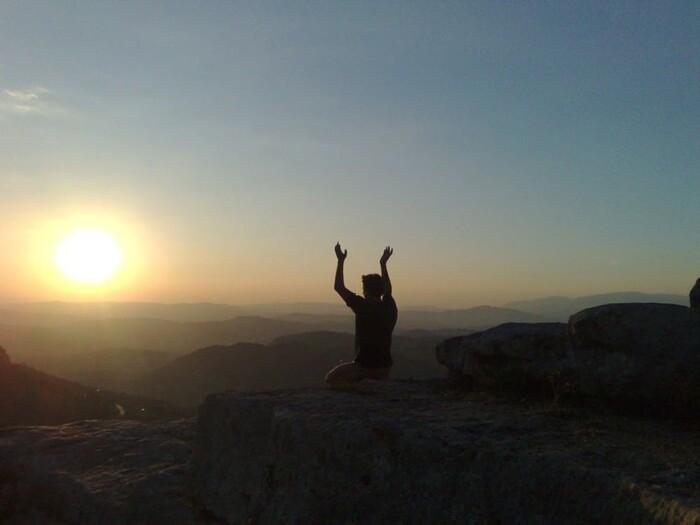 Man meditating on a cliff at sunrise.