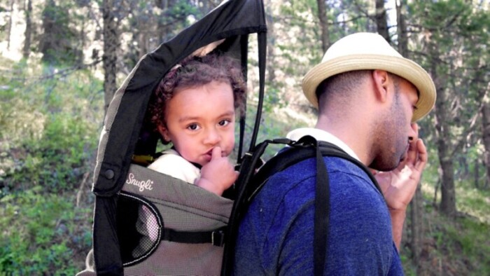 Man hiking with toddler carrier on his back.