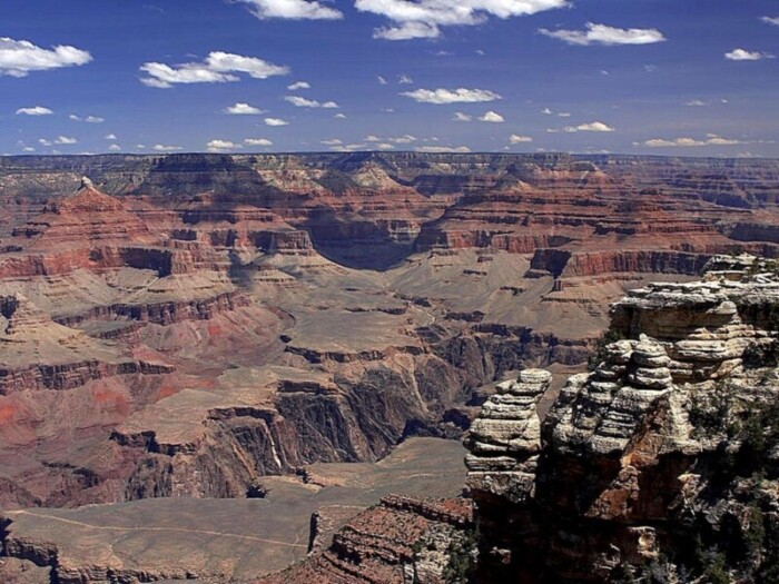 View of the Grand Canyon under a blue sky with clouds