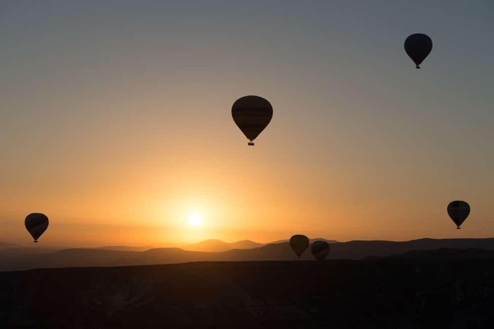 Four hot air balloons against a sunrise.