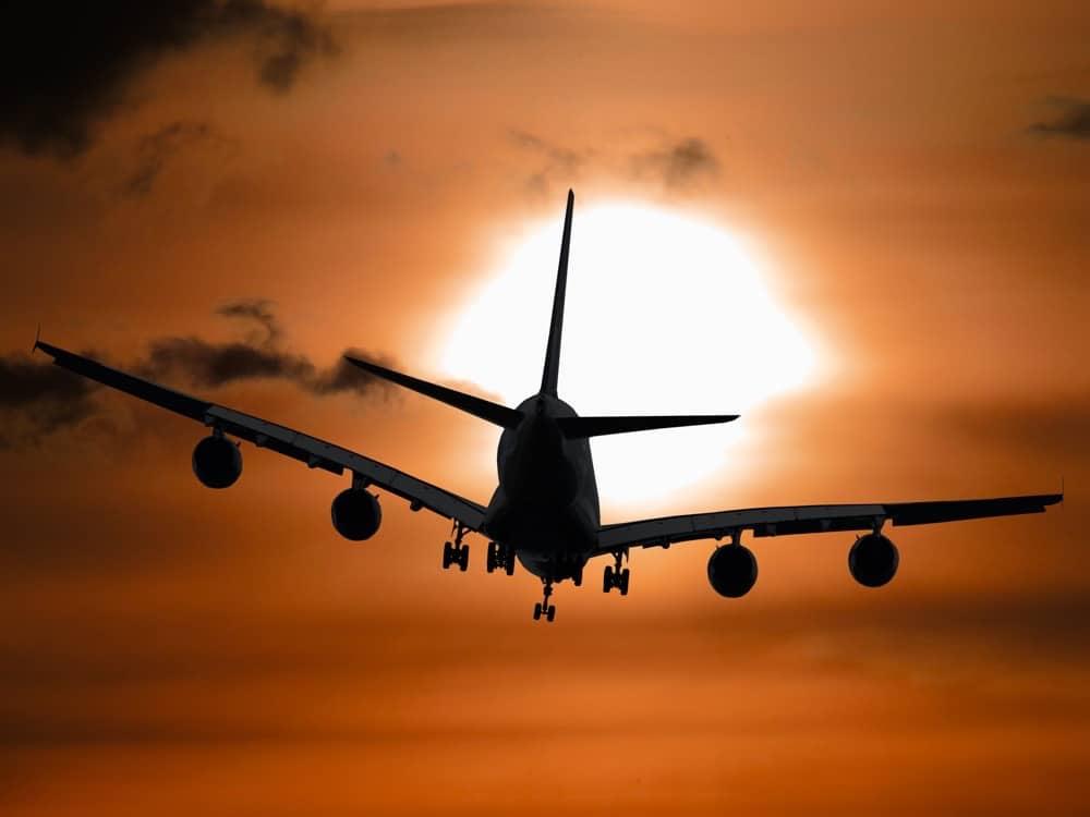 Silhouette of airplane against sunset