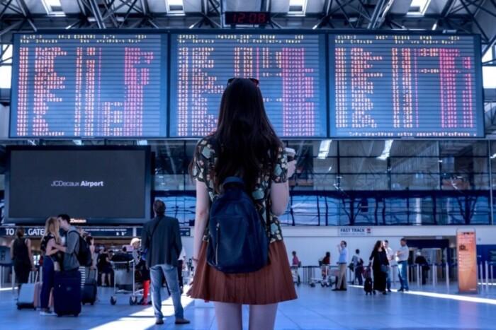 Woman stands in front of arrival and departure board at an airport