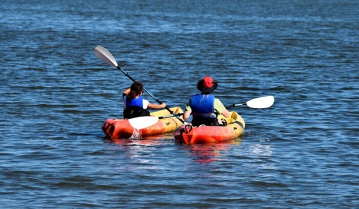 Two people in blue life jackets paddle orange kayaks on the river