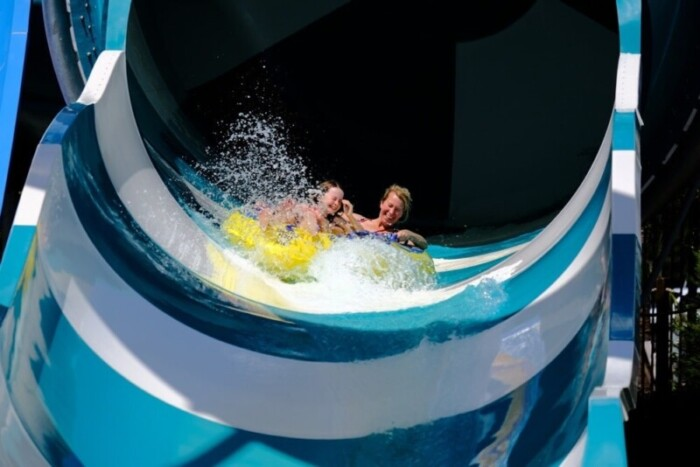 two people exit a large water slide with a splash.