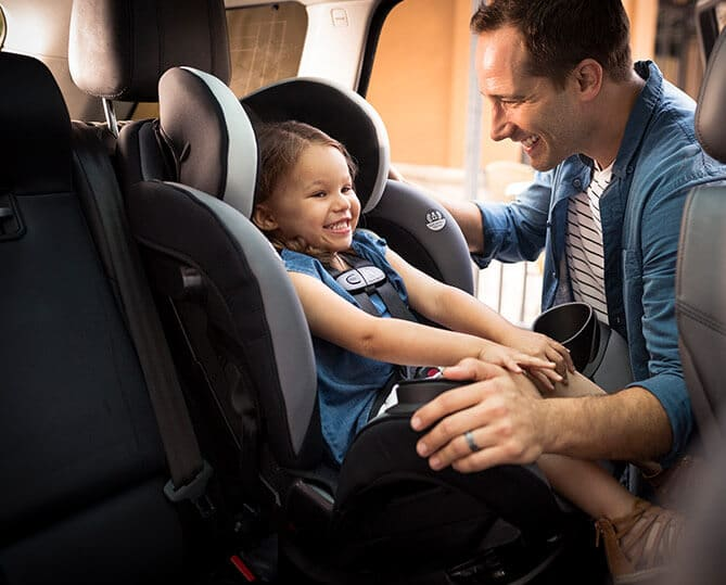 Man securing young girl in a car seat