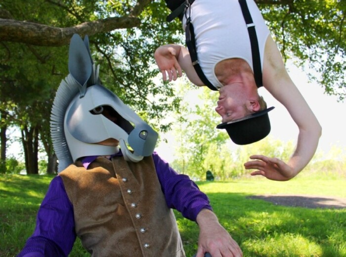 Person with a horse mask faces a man hanging upside down.
