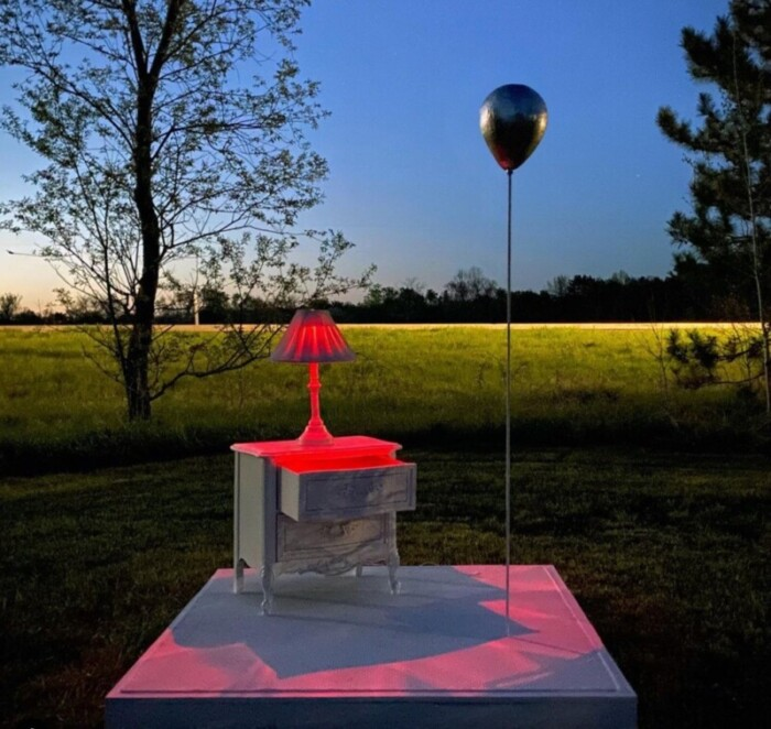 Sculpture of a table, lamp, and balloon.