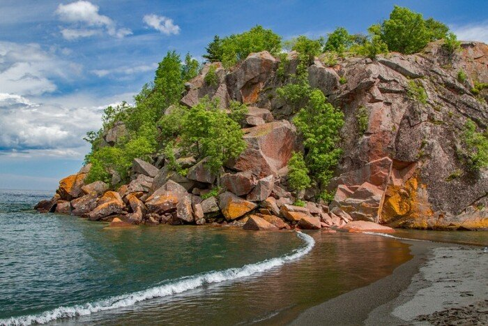 scenic view of the beach, with rock formation at the back with foliage and water in the front of the beach