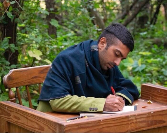 Man writes at an outdoor desk.