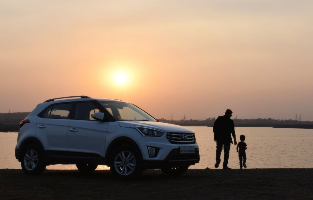 person and child with car and sunset