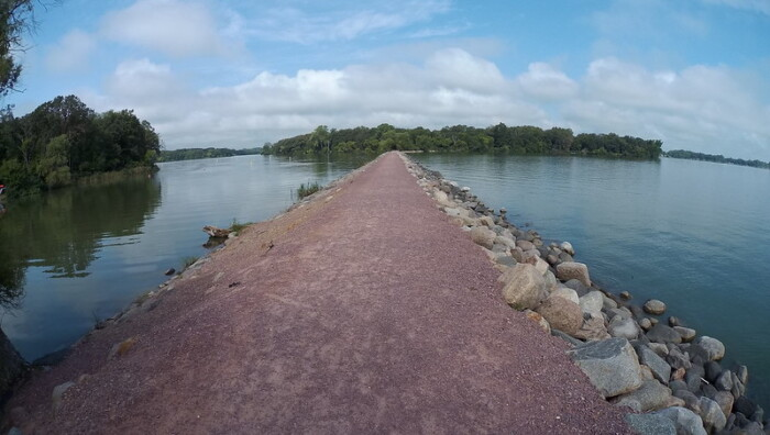 panoramic view of a small road leading to another island at the back with lake water at  both sides