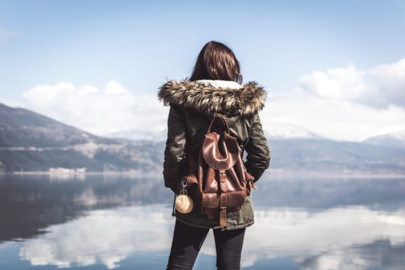 A woman with a backpack staring beholding a lake
