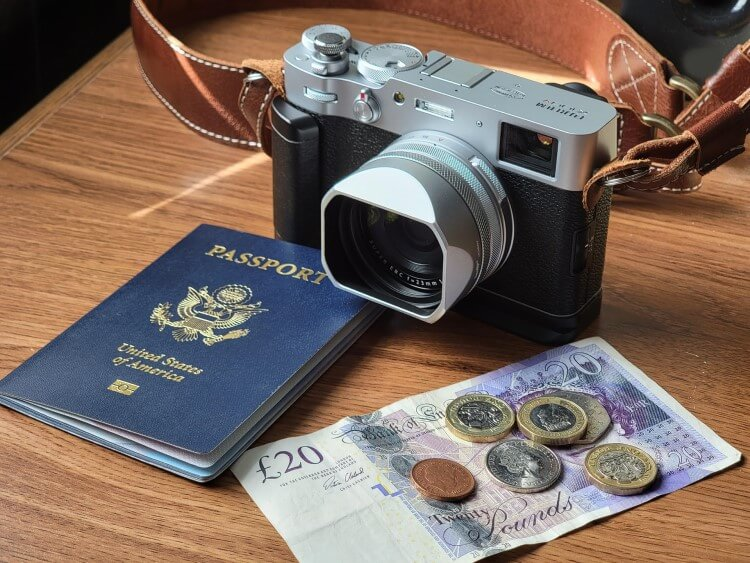 Camera, passport, and money on a wooden table