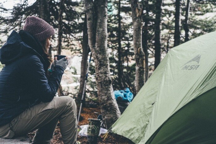 Woman drinks coffee next to a tent