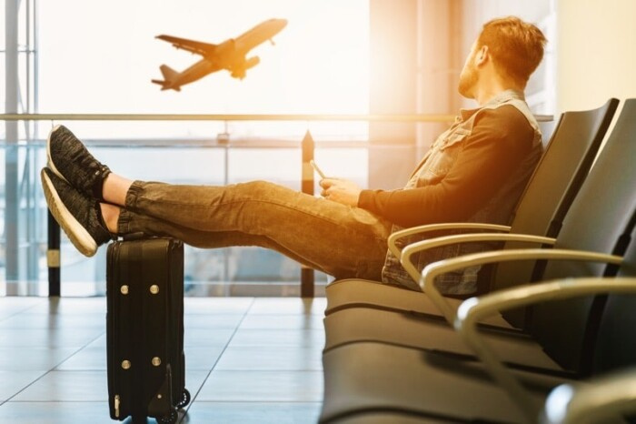 Man props feet on suitcase